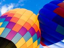 Due mongolfiere variopinte contro cielo blu Fotografia Stock Libera da Diritti