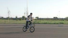 Due motociclisti adolescenti che esercitano i movimenti acrobatici che guidano le biciclette su una ruota all'aperto - video d archivio