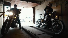 Due motociclisti che prendono le motociclette su ordinazione al garage video d archivio
