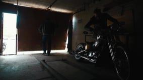 Due motociclisti che prendono motocicletta su ordinazione dal garage video d archivio