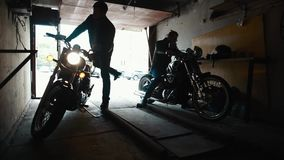 Due motociclisti che prendono motocicletta su ordinazione dal garage archivi video