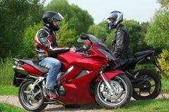 Due motociclisti che si levano in piedi sulla strada campestre immagine stock