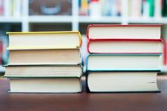 Due mucchi dei libri con la biblioteca nel fondo Fotografia Stock Libera da Diritti