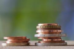 Due mucchi della dimensione e del colore differenti delle monete impilati su a vicenda sul fondo blu e verde variopinto dello spa fotografie stock