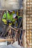Due muratori stanno lavorando con un tagliente immagini stock
