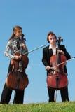 Due musicisti giocano i violoncellos contro il cielo Fotografie Stock Libere da Diritti