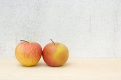Due nature morte della mela sul fondo del compensato e del muro di cemento Immagini Stock Libere da Diritti