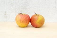 Due nature morte della mela sul fondo del compensato e del muro di cemento Fotografia Stock