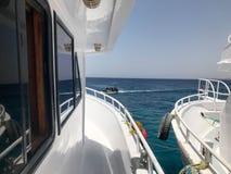 Due navi bianche, una fodera di crociera, yacht, barche che stanno molto vicino, bordo per imbarcare contro il mare blu del sale, Immagine Stock Libera da Diritti