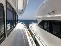 Due navi bianche, una fodera di crociera, yacht, barche che stanno molto vicino, bordo per imbarcare contro il mare blu del sale, Fotografia Stock