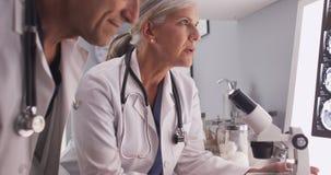Due neurologi bianchi maturi che studiano i raggi x fotografia stock