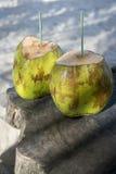 Due noci di cocco verdi sulla Tabella di legno rustica Immagini Stock Libere da Diritti