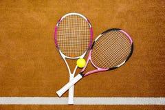 Due nuove racchette di tennis rosa con una pallina da tennis su un campo in argilla o Fotografie Stock Libere da Diritti