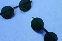 Due occhiali da sole neri alla moda con i vetri rotondi si trova su una coperta fatta del tessuto blu-chiaro molle e lanuginoso d fotografia stock