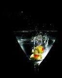 Due olive che spruzzano nel vetro del Martini Immagini Stock
