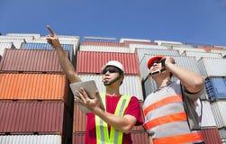 Due operai che si levano in piedi prima dei contenitori Fotografia Stock Libera da Diritti