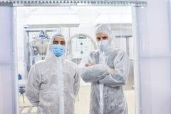 Due operai che stanno in vestiti protettivi immagini stock