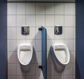 Due orinali su una costruzione di utilità pubblica con un muro divisorio di plastica blu davanti ad una parete piastrellata bianc immagini stock