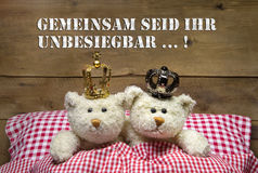 Due orsacchiotti beige nell'amore che si trova a letto con le corone. Fotografia Stock Libera da Diritti