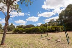 Due oscillazioni vuote su erba con un piccolo albero nella priorità alta sotto un cielo blu con alcune nuvole bianche fotografia stock libera da diritti