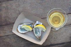 Due ostriche con il limone e un vetro di vino bianco fotografia stock