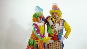 Due pagliacci divertenti che cantano e che ballano contro il fondo bianco video d archivio