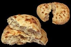 Due pagnotte lacerate del pane di Pitta isolate su fondo nero Fotografia Stock