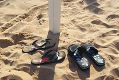 Due paia dei flip-flop delle pantofole hanno spruzzato la spiaggia di sabbia Fotografia Stock Libera da Diritti
