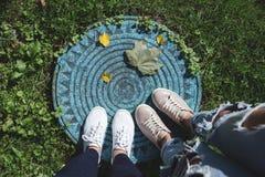 Due paia delle gambe del ` s della donna e delle foglie cadute sulla botola Immagini Stock Libere da Diritti