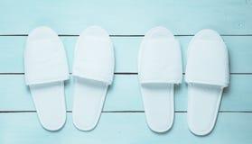 Due paia delle pantofole bianche dell'hotel su un pavimento di legno blu Vista superiore fotografia stock