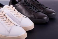 Due paia delle scarpe delle scarpe da tennis su fondo nero Scarpa in bianco e nero Fotografia Stock Libera da Diritti