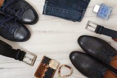 Due paia delle scarpe di cuoio nere del ` s degli uomini, due cinghie per gli uomini, jeans Fotografia Stock Libera da Diritti