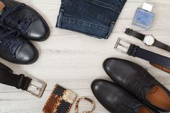 Due paia delle scarpe di cuoio nere del ` s degli uomini, due cinghie per gli uomini, jeans Fotografie Stock