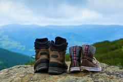 Due paia delle scarpe - pulite e sporche nel soggiorno del fango sulla roccia Immagini Stock Libere da Diritti