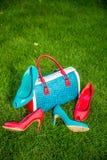 Due paia delle scarpe verdi e rosse e la borsa mettono sull'erba Immagini Stock Libere da Diritti