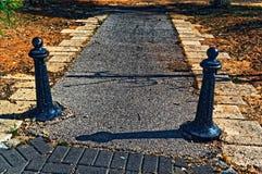 Due pali neri e un marciapiede fra loro fotografie stock libere da diritti
