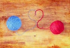 Due palle della lana con cuore modellano sopra il bordo di legno Fotografia Stock