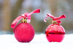 Due palle rosse di natale fuori in neve Fotografia Stock Libera da Diritti