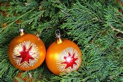Due palle variopinte di Natale sugli aghi verdi del pino Fotografia Stock