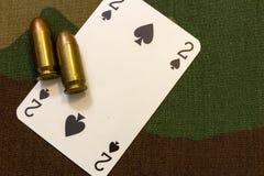 Due pallottole e carte da gioco d'annata della pistola sul fondo senza cuciture del modello del cammuffamento militare Concetto d immagine stock libera da diritti
