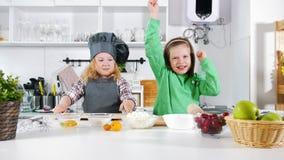 Due panettieri prescolari delle bambine si divertono durante la cottura le torte di formaggio e dei dessert stock footage