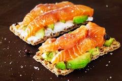 Due panini croccanti con l'avocado ed il salmone affumicato Fondo dell'ardesia fotografie stock libere da diritti