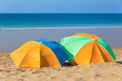 Due parasoli variopinti sulla spiaggia dal mare Fotografie Stock
