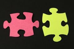 Due parti del puzzle su fondo di carta nero Fotografie Stock