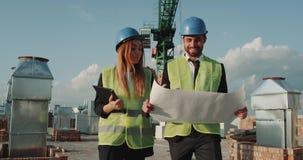 Due partner dal cantiere che camminano intorno alla costruzione sul tetto e che discutono il piano dell'nuovi appartamenti archivi video