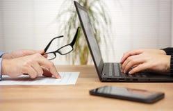 Due partner sono esaminanti ed esaminanti il documento in ufficio, wom fotografie stock