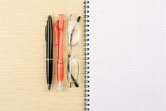 Due penne, galsses e taccuini fotografia stock libera da diritti