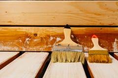 Due pennelli che si trovano sulla superficie parzialmente a stecche dipinta immagini stock