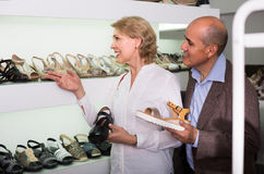 Due pensionati che scelgono insieme le paia delle scarpe nel deposito di modo Fotografia Stock