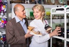 Due pensionati che scelgono insieme le paia delle scarpe nel deposito di modo Fotografia Stock Libera da Diritti